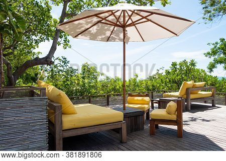 Wooden, Yellow Sofa Couch With Umbrella At The Outdoor Patio. With Green Tree And Blue Sky Nature Ba