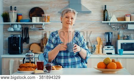 Happy Senior Woman Holding Cup Of Coffee While Looking At Camera In Ktichen During Breakfast. Authen
