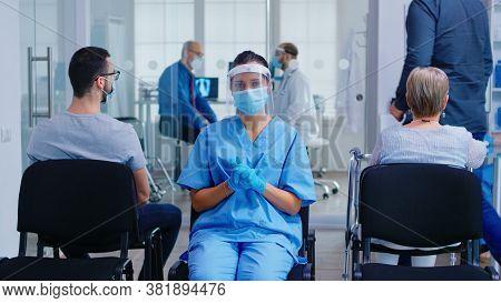 Medical Nurse With Face Mask And Visor Against Coronavirus Wearing Blue Uniform In Hospital Waiting