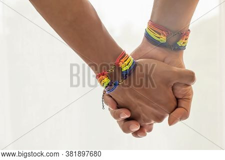 Close Up Shot Of Asian Male Couple Holding Hands With  Gay Pride Rainbow Awareness Wristbands. Lgbt,