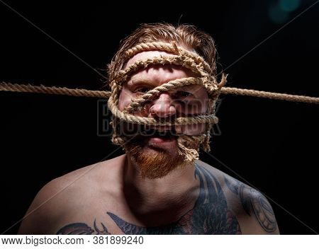 Photo Of Binded Tattooed Man With Rope On Face