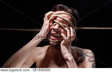 Photo Of Binded Brunette Man Trying Tear The Rope On Face