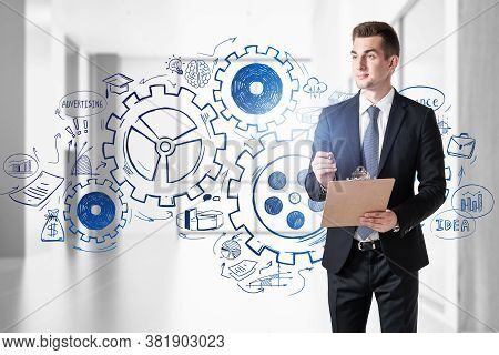 Young Businessman With Clipboard Walking In Blurry Office With Double Exposure Of Gears Sketch. Tone