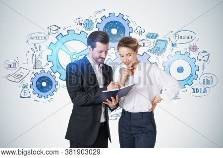Businessman And Businesswoman With Notebook Standing Near Concrete Wall With Gears Sketch