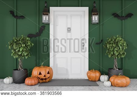 Carved Pumpkins And Bats Near White Front Door Of Modern House With Green Walls And Trees In Pots. C