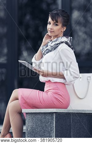 Young business woman using tablet computer at office building Stylish fashion model in white shirt and pink pencil skirt