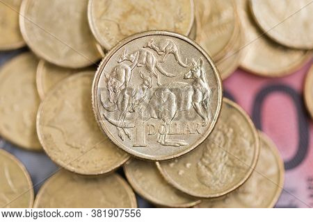 An Australian One Dollar Coin Untop Of A Stack Of Coins And Bank Notes.