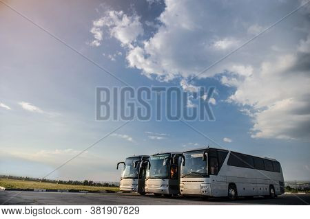 Three Buses Staying In The Parking Lot. Front View Of The Buses With Blue Sky And Clouds.
