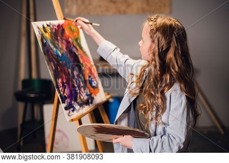 A Little Girl Artist Draws A Picture With A Brush In The Studio. A Talented Young Schoolgirl