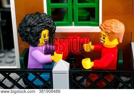 Tambov, Russian Federation - June 26, 2020 Lego Couple Minifigures With Mugs Sitting On The Terrace.
