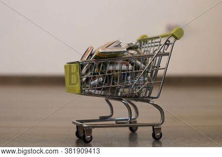 Small Cart With Sweets In The Form Of Money In A Round Plan. A Cart With Sweets On The Floor. Grocer