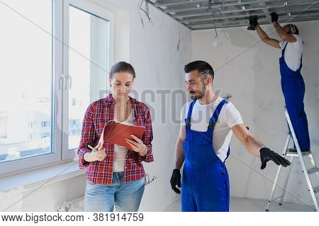 The Woman Checks The Work Of The Builders In The Apartment And Writes A Note