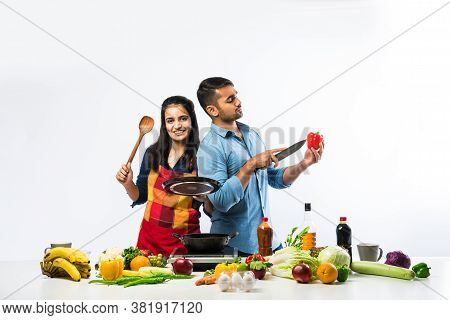 Indian Couple Cooking - Attractive Wife And Handsome Husband In Kitchen With Fresh Green Vegetables