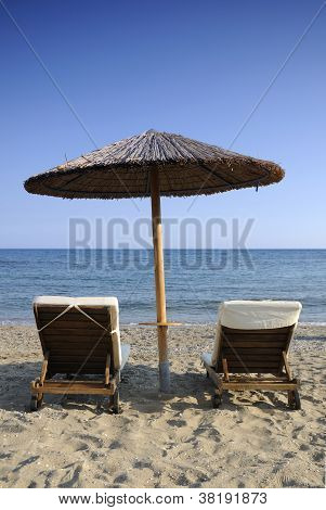 Beach umbrella and two chairs over the sea