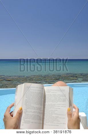 Girl reading a book over the sea
