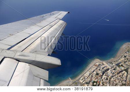 Sky sea and island seen through window of an aircraft