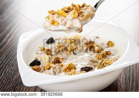 Metallic Spoon With Cereal Breakfast Above Bowl With Granola And Yogurt On Dark Wooden Table