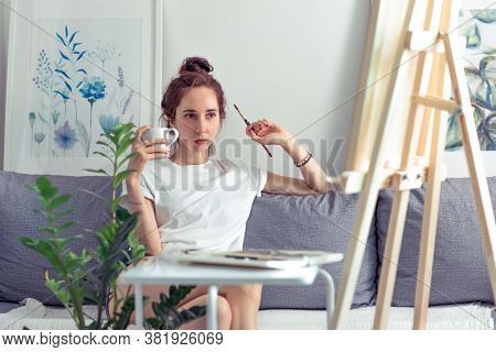 Beautiful Woman Artist, Sitting On Sofa At Home, Looking At A Painting, Holding A Mug Of Coffee With