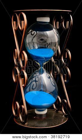 Hourglass With Purple Sand Isolated On A Black Background