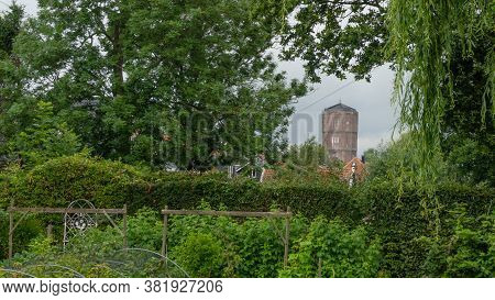 Framed View On The Brick Built Water Tower Of Kwadijk, Looking Through The Lush Greenery Of A Backya