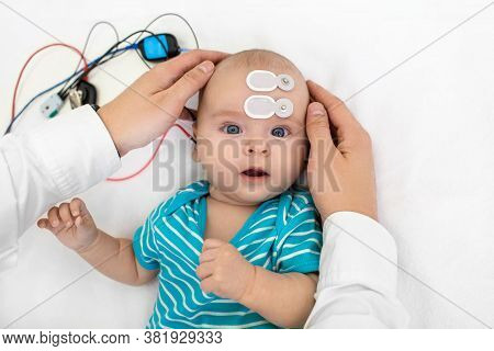 Newborn Hearing Screening And Diagnosis At The Hospital. Baby Having Hearing Screening With Special