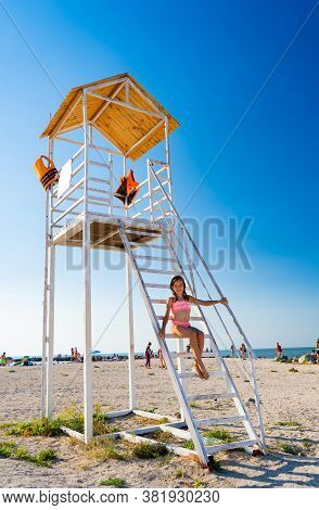 A Teenage Girl Sitting On The Stairs A Lifeguard Tower On The Beach Against A Cloudless Sky.