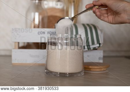 The Girl Spilled A Spoonful Of Sugar Into A Jar. The Girl Takes Sugar From The Can. The Girl Pours S