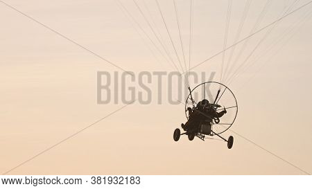 Silhouette Of The Paramotor Tandem Gliding And Flying In The Air. Copy Space High Quality Photo
