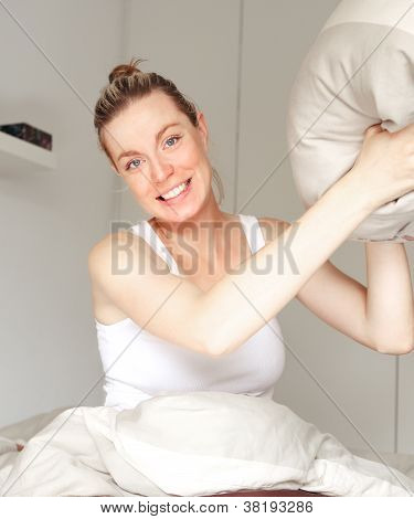 Playful Woman Throwing A Pillow