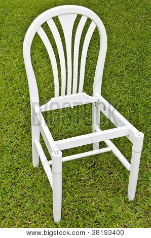 Uncomplete White Chair On Green Grass