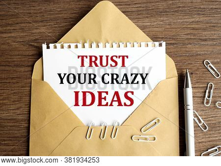Trust Your Crasy Ideas. Text On White Paper In An Envelope On A Nineteen Table, Near White Paper Cli
