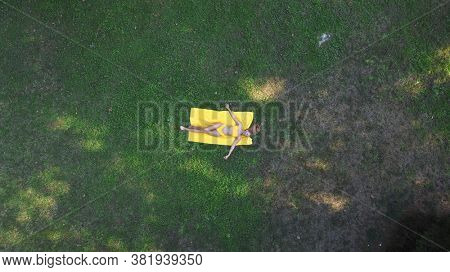 woman lying on the grass photographed by a drone