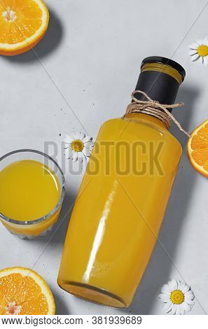 A Glass Bottle With Orange Juice Tied With A Thread, With A Mock-up For Text, Next To It Are Halves