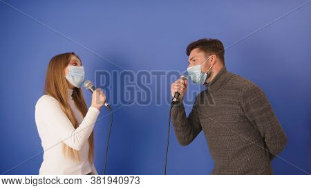 Young Couple Singing Karaoke With Social Distancing And Medical Masks. High Quality Photo