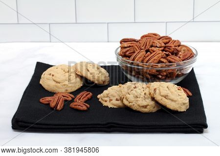 Fresh Baked Pecan Cookies Also Know As Sandies On A Black Napkin In Front Of A Bowl Of Pecan Halves.