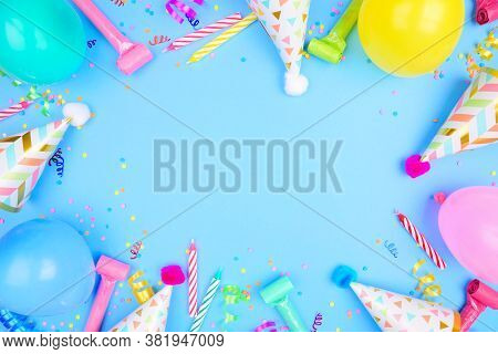 Birthday Party Frame On A Blue Background. Top View With Confetti, Balloons, Party Hats And Streamer
