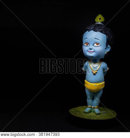 Cute And Innocent Idol Of Hindu God Lord Krishna As A Child With Black Background. Celebrated During