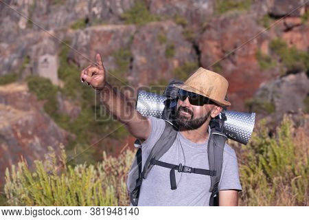 Hispanic Male Trekker With Sunglasses Smiling And Pointing Out Of The Frame