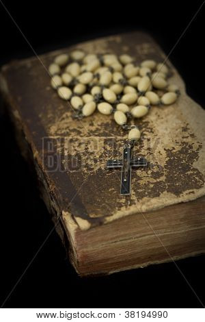 ancient worn off book with prayer beads