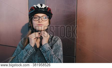 Portrait Shot Of Young Caucasian Woman Adjusting Her Safety Gear, Helmet. Getting Ready For Rollerbl