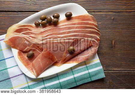 Balkan Cuisine . Slices Of Prsut: Dry-cured Ham,  Balkan Version Of Prosciutto. Dark Rustic Table. C