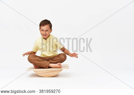 Small Boy Is Sitting On A Special Simulator For Training The Vestibular Apparatus. To Maintain Balan