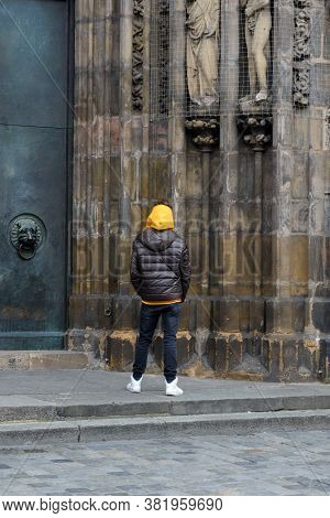 Nuremberg, Germany. A Young Man Examines The Details Of The Frauenkirche Catholic Church In Nurember