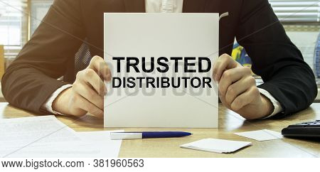 Man Take A Paper With Text Trusted Distributor On The Shirt With Office Background