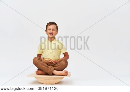 Small Boy Is Sitting On A Special Simulator For Training The Vestibular Apparatus. To Keep Your Bala
