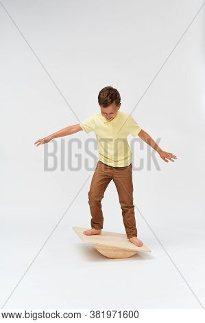 Little Boy Stands On A Special Simulator For Training The Vestibular Apparatus. To Keep The Balance