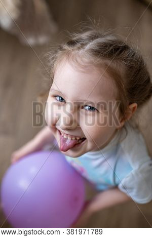 A Cheerful Little Blonde Girl With A Balloon In Her Hands Laughs And Shows Her Tongue. Close Up. The