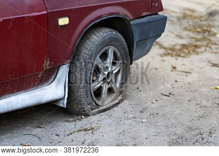 Car With Deflated Wheel On Street. Old Red Car With Deflated Wheel Parked On Paved Street In Sunligh
