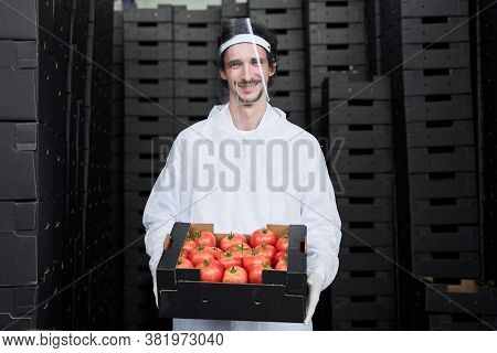 Joyous Warehouse Worker Standing Among Cardboard Boxes