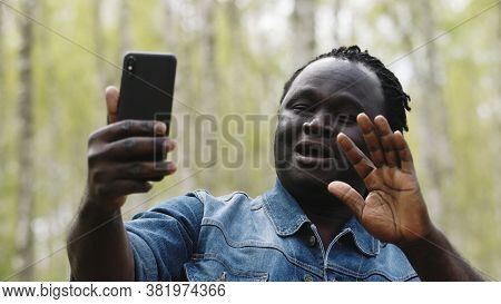 African Man Taking Selfies Or Having Videocall On His Smartphone In The Nature. High Quality Photo